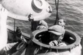 An Italian diver in the diving bell, of the TITAN trailer is preparing to dive at the U-133 shipwreck. The photo was taken by the German war correspondent Werner Hartmann on April 4, 1942. Behind the bell, the captain of an officer of the Italian Royal Navy, Regia Marina Italiana, and a German Navy sailor, the Kriegsmarine, with the distinctive hat. Archive Axel Urbanke U-boot im focus.